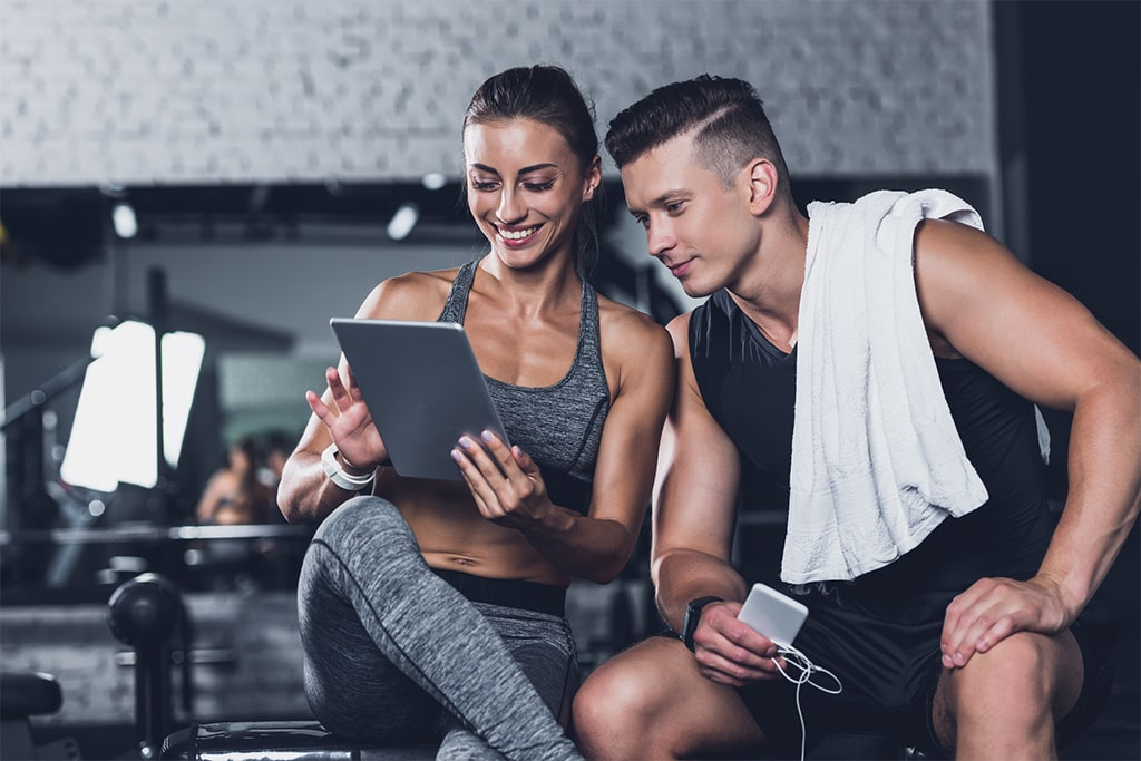 S2 Method smiling sportive couple using tablet in gym